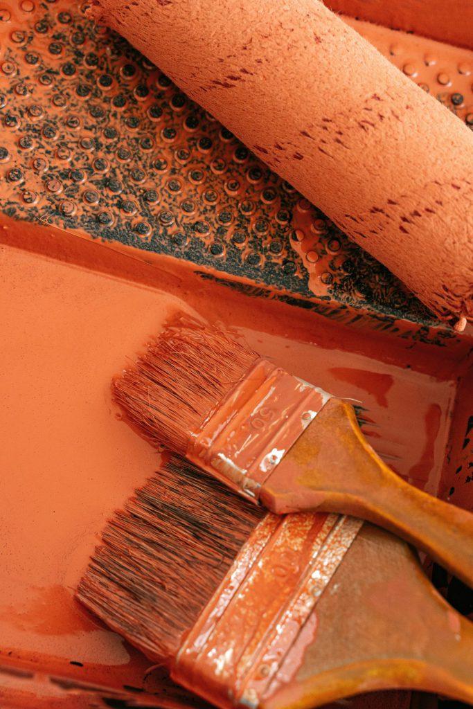 Pensseleitä ja maalaustela. Oranssia maalia.