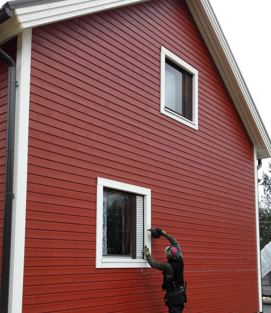 Työmies viimeistelee punaisen talon ulkoverhoilua.