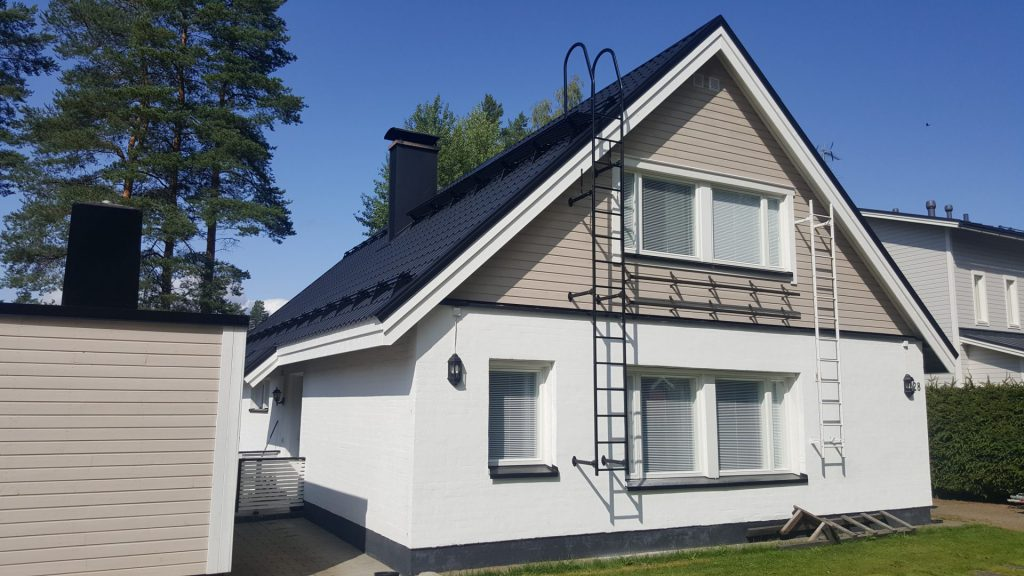 Valkoinen talo, jossa uusittu mustanharmaa katto.